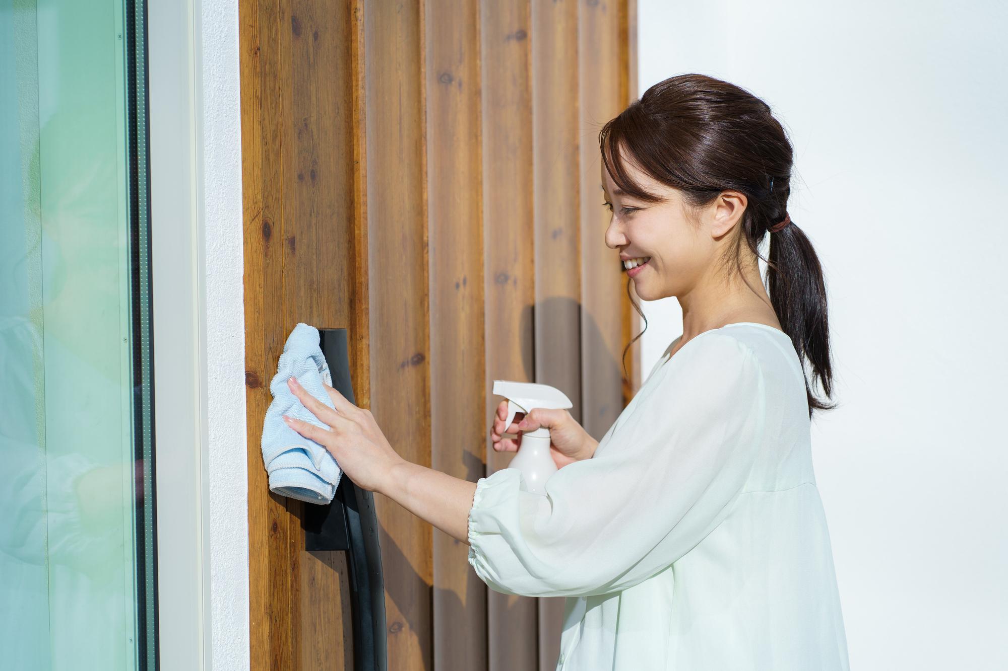 玄関を除菌する女性